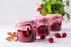 Jars with raspberry jam placed in rows and fresh raspberry. On white wooden table Royalty Free Stock Image