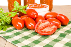 Jars of sauce with paste tomatoes and basil Royalty Free Stock Photography