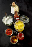 Jars of sauces and toppings over dark background Royalty Free Stock Images