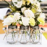 Jars with small white and green bouquets Stock Photography