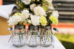 Jars with small white and green bouquets Stock Photos