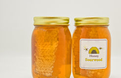 Jars of Sour Wood Honey. Sour wood honey in clear glass jars along with honeycomb Stock Images