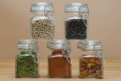 Jars with spices. Some glass jars with different spices on a bamboo surface royalty free stock photo