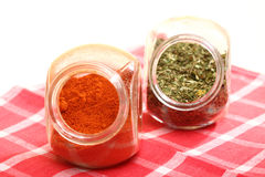 Jars with spices paprika and lovage isolated Royalty Free Stock Photos