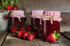 Jars Strawberry Preserves. Three pint jars of strawberry preserves, fresh strawberries and steel bucket with strawberry plant blurred in background Royalty Free Stock Photos