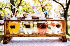 Jars with a tap on a wooden stand in a garden. Royalty Free Stock Photo