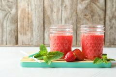 Jars with tasty strawberry smoothie. On wooden board stock photography