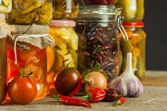 Jars with variety of pickled vegetables. Carrots, field garlic, parsley in glas. Preserved food. Fermented preserved vegetarian fo. Od concept Stock Photo