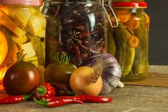 Jars with variety of pickled vegetables. Carrots, field garlic, parsley in glas. Preserved food. Fermented preserved vegetarian fo. Od concept Stock Photos