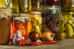 Jars with variety of pickled vegetables. Carrots, field garlic, parsley in glas. Preserved food. Fermented preserved vegetarian fo. Od concept Royalty Free Stock Image