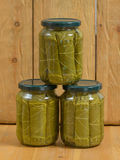 Jars of various pickled vegetables. Canned grape leaves. Stock Photos