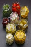 Jars with various preserved food. Opened jars with various preserved food on dark board Royalty Free Stock Image