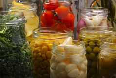 Jars with various preserved food. Opened jars in pantry with various preserved food Stock Photos