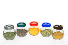Jars with various spices. Jars with various exotic spices (fenugreek,allspice tree, turmeric, cardamom, curry) isolated on white background Royalty Free Stock Image