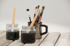Jars of watercolor and paint brushes on wooden table Stock Photography