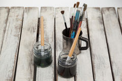 Jars of watercolor and paint brushes on wooden table Stock Image