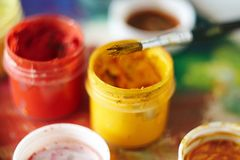 Jars of  gouache paint, as well as a paint brush royalty free stock image