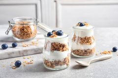 Jars with yogurt, berries and granola. On  table Royalty Free Stock Images