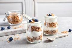 Jars with yogurt, berries and granola royalty free stock images