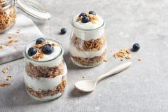 Jars with yogurt, berries and granola. On  table Stock Image