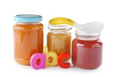 Jars with yummy baby food and spoon on background Royalty Free Stock Photo