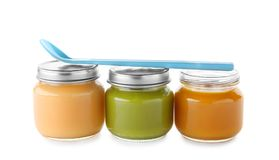 Jars with yummy baby food and spoon Royalty Free Stock Images