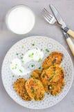 Jarscy quinoa, marchewki, kolendrowej i zielonej cebuli fritters, słuzyć z jogurtem na talerzu, odgórny widok Obrazy Stock