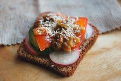 Jarska kanapka z rzodkwią, pomidorem, ziele i warzywami na drewnianym tle, obraz stock