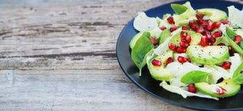 Jarska sałatka z avocado, zieleniami, liśćmi, granatowem i letuce liśćmi, Drewniany wieśniaka stół obraz royalty free