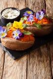 Jarski cały piec batat dekorujący z jadalnymi kwiatami słuzyć z kumberlandem na desce pionowo obraz royalty free