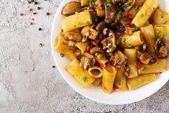 Jarski makaronu rigatoni z pieczarkami i chili pieprzami zdjęcia stock