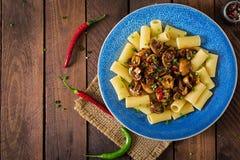 Jarski makaronu rigatoni z pieczarkami i chili pieprzami w błękitnym pucharze zdjęcie stock