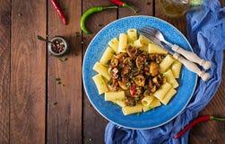 Jarski makaronu rigatoni z pieczarkami i chili pieprzami w błękitnym pucharze fotografia royalty free