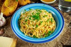 Jarski Włoski makaronu spaghetti Aglio E Olio z czosnku chlebem, czerwonym chili płatkiem, pietruszką, parmesan serem i glas, Fotografia Royalty Free