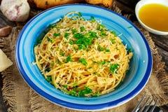 Jarski Włoski makaronu spaghetti Aglio E Olio z czosnku chlebem, czerwonym chili płatkiem, pietruszką, parmesan serem i glas, dal Obraz Stock
