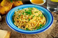 Jarski Włoski makaronu spaghetti Aglio E Olio z czosnku chlebem, czerwonym chili płatkiem, pietruszką, parmesan serem i glas woda Obraz Stock