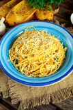 Jarski Włoski makaronu spaghetti Aglio E Olio z czosnku chlebem, czerwonym chili płatkiem, pietruszką, parmesan serem i glas woda Zdjęcie Royalty Free