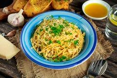 Jarski Włoski makaronu spaghetti Aglio E Olio z czosnku chlebem, czerwonym chili płatkiem, pietruszką, parmesan serem i glas woda Obrazy Royalty Free