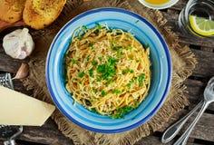 Jarski Włoski makaronu spaghetti Aglio E Olio z czosnku chlebem, czerwonym chili płatkiem, pietruszką, parmesan serem i glas woda Zdjęcie Stock