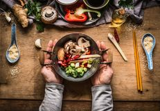 Jarskiego fertanie dłoniaka kulinarny przygotowanie Kobiet żeńskie ręki trzyma małego wok garnek z siekającymi warzywami dla fert obrazy royalty free