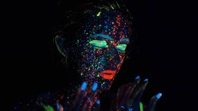 Jarzeniowa farba na dziewczyny twarzy Portret piękna młoda kobieta z rozjarzoną farbą na jej twarzy zdjęcie wideo
