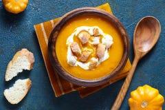 Jarzynowa kremowa polewka z marchewką, banią i krakers, Odgórny widok na ciemnym kreatywnie tle dieta zdrowy posiłek Obraz Royalty Free