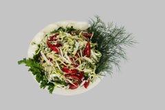 Jarzynowa sałatka pomidor, kapusta i zielenie na szarym tle -, ?lipping ?cie?ka fotografia stock
