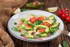 Jarzynowa sałatka z avocado, arugula, rzodkwią, wapnem i oliwa z oliwek, Żywienioniowy zdrowy jedzenie drewniany tło wieśniak Odg zdjęcia royalty free