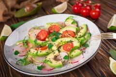 Jarzynowa sałatka z avocado, arugula, rzodkwią, wapnem i oliwa z oliwek, Żywienioniowy zdrowy jedzenie drewniany tło wieśniak Odg obraz royalty free