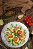 Jarzynowa sałatka z avocado, arugula, rzodkwią, wapnem i oliwa z oliwek, Żywienioniowy zdrowy jedzenie drewniany tło wieśniak Odg zdjęcia stock