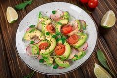 Jarzynowa sałatka z avocado, arugula, rzodkwią, wapnem i oliwa z oliwek, Żywienioniowy zdrowy jedzenie drewniany tło wieśniak Odg obrazy royalty free