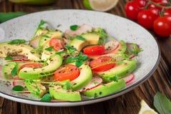 Jarzynowa sałatka z avocado, arugula, rzodkwią, wapnem i oliwa z oliwek, Żywienioniowy zdrowy jedzenie drewniany tło wieśniak Odg obraz stock