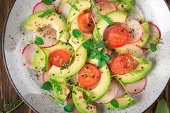 Jarzynowa sałatka z avocado, arugula, rzodkwią, wapnem i oliwa z oliwek, Żywienioniowy zdrowy jedzenie drewniany tło wieśniak Odg obrazy stock