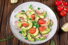 Jarzynowa sałatka z avocado, arugula, rzodkwią, wapnem i oliwa z oliwek, Żywienioniowy zdrowy jedzenie drewniany tło wieśniak Odg fotografia stock